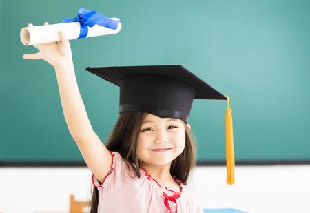 Portret van leuk schoolmeisje met afstuderen hoed in de klas