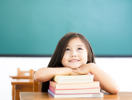copyspace: happy little girl with books and thinking in classroom