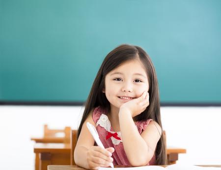 niña feliz escribiendo en el escritorio en el aula