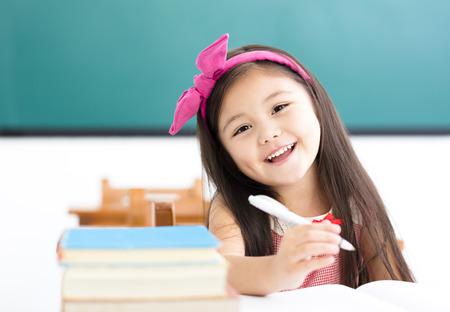 교실에서 책상에 쓰기 행복 한 작은 소녀