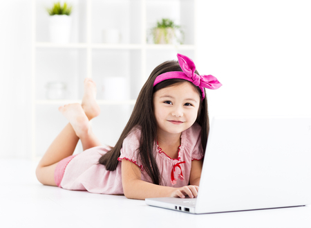 Happy little girl working with a laptop