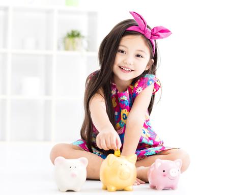 돼지 저금통을 가지고 노는 행복 한 작은 소녀 스톡 콘텐츠