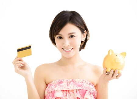young woman showing credit card and piggy bank