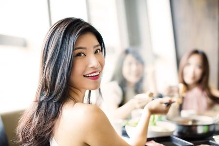 Красивая молодая группа женщин, едят горячий горшок