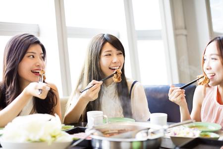 Happy jonge vrouwen groep het eten van hete pot