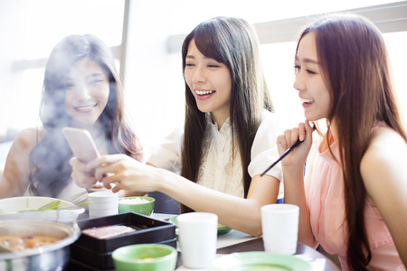 young Women group  Eating hot pot and taking picure by phone