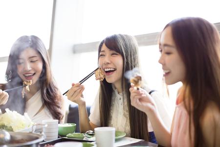 mujeres juntas: feliz grupo de jóvenes mujeres olla caliente Comer