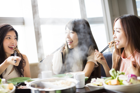 table: happy young Women group  Eating hot pot