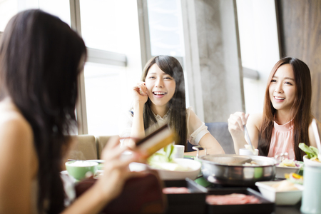 resting: young Women group  Eating hot pot and showing credit card