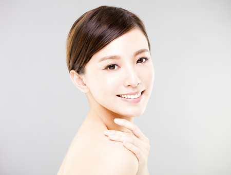 young smiling woman face with gray background Banco de Imagens - 75480164