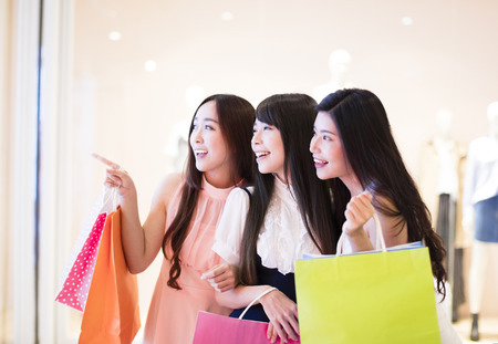 customer: happy woman group holding shopping bags walking at  mall