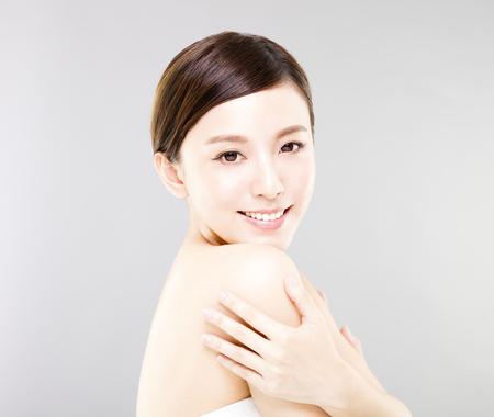 Jong lachende vrouw gezicht met grijze achtergrond
