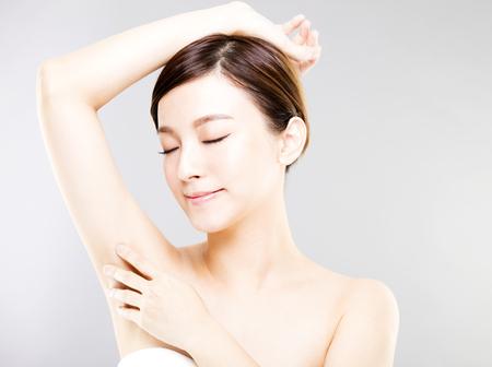 Junge schöne Frau mit perfekter Haut und Achselhöhle Pflege Standard-Bild - 75624075