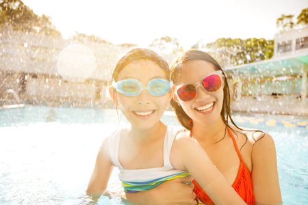Happy mother and daughter playing in swimming pool Stock fotó