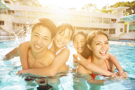Happy family playing in swimming pool