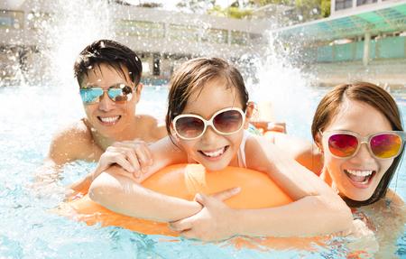 Glückliche Familie spielen im Schwimmbad Standard-Bild - 75982561