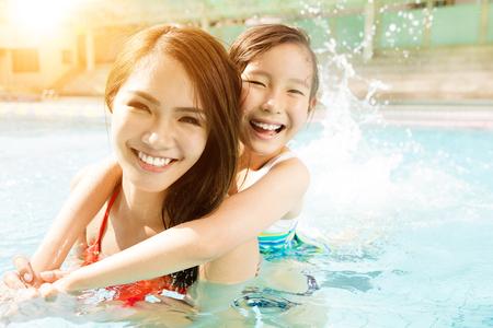 家庭: 幸福的母親和女兒在游泳池玩