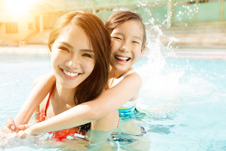 Feliz madre e hija jugando en la piscina Foto de archivo