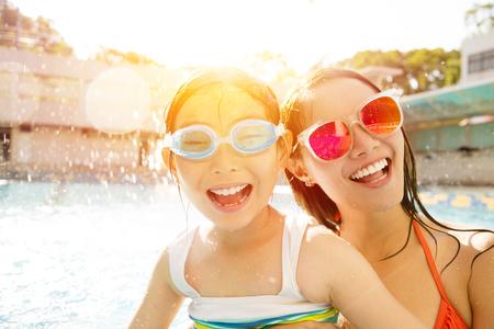 Glückliche Mutter und Tochter spielen im Schwimmbad