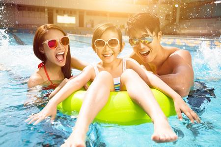 mojada: Familia feliz que juega en la piscina