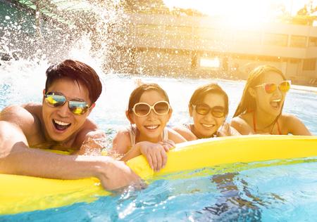 Gelukkig gezin spelen in zwembad Stockfoto