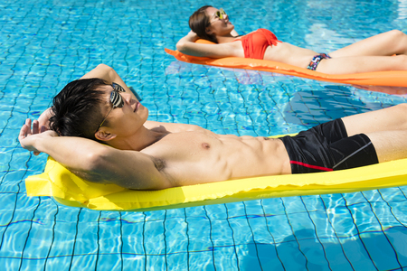 asian guy: young couple relaxing on inflatable raft at swimming pool Stock Photo
