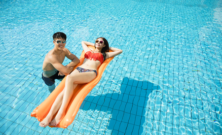 young couple relaxing on inflatable raft at swimming pool Standard-Bild