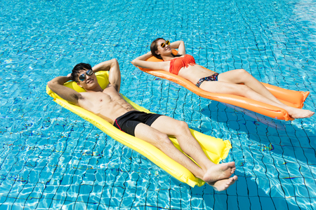 young couple relaxing on inflatable raft at swimming pool Imagens