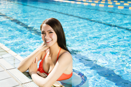 beautiful young woman relaxing in swimming pool Stock Photo