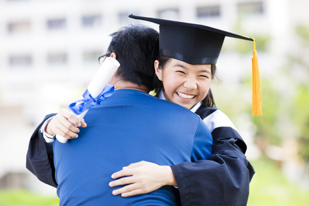 female student and family hug celebrating graduation