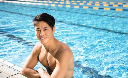 Hübscher lächelnder junger Mann im Schwimmbad
