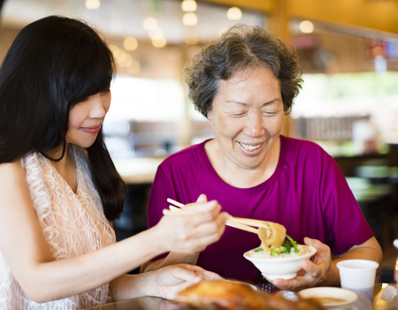 Happy  daughter and senior mother enjoy eating in restaurant photo