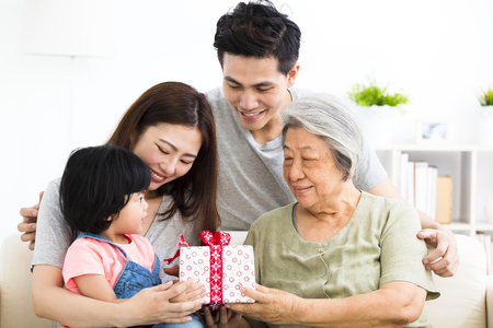 happy  little girl giving  present to her grandmother 스톡 콘텐츠