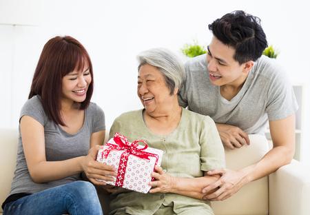 할머니에게 선물을주는 행복한 젊은 커플