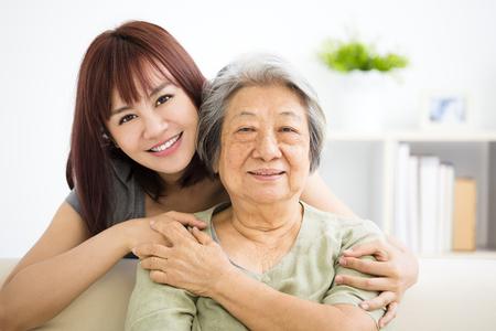 Großmutter und Enkelin. Junge Frau nimmt sorgfältig Pflege der alten Frau Standard-Bild - 76987503