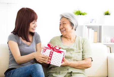 할머니에게 선물을주는 행복 한 젊은 여자