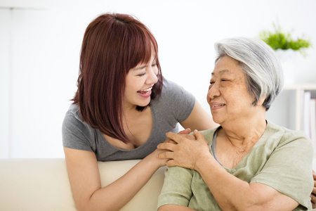 Grandmother and granddaughter. Young woman carefully takes care of old woman photo