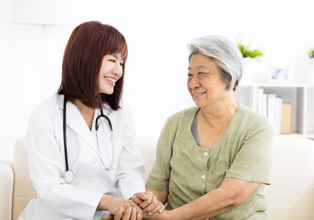 young smiling home caregiver  with senior woman photo