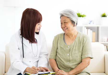 young smiling home caregiver  with senior woman