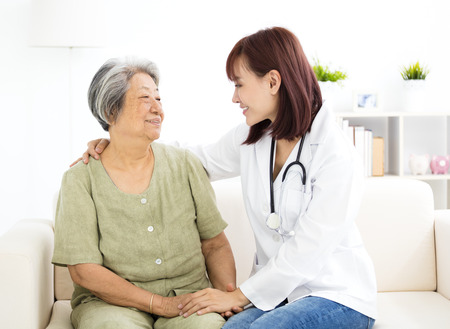help: young smiling home caregiver  with senior woman Stock Photo