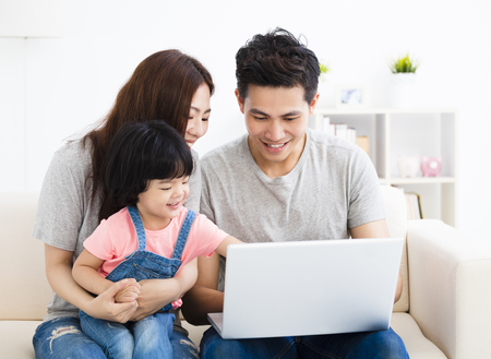 happy family using laptop in living room