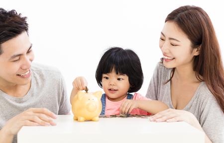 돼지 저금통에 동전을 퍼팅 딸과 함께 행복 한 가족