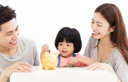 happy family with daughter putting coins into piggy bank  Standard-Bild