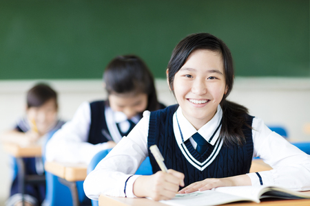 smiling student girl in classroom and her friends in background