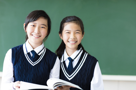 smiling  teenager student girls in  classroom photo