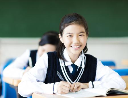 Sonriente estudiante chica en el aula y sus amigos en el fondo