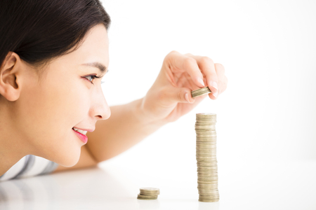 heap: young woman put coins to stack , Saving money concept