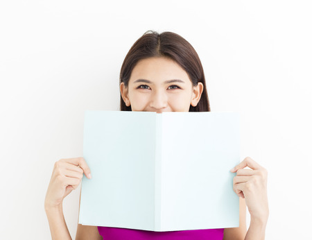 Smiling young  woman reading  book against  white wall