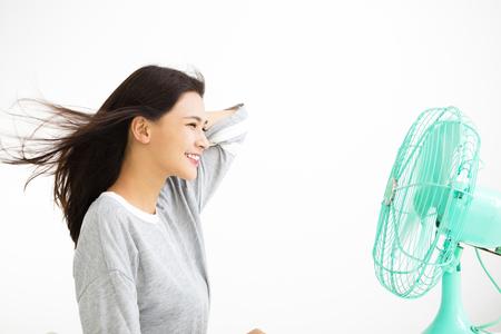 전기 팬에 의해 자신을 냉각 웃는 여자