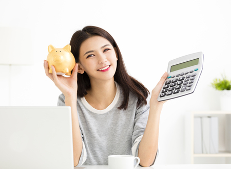 Young Woman showing Calculator  and Piggybank